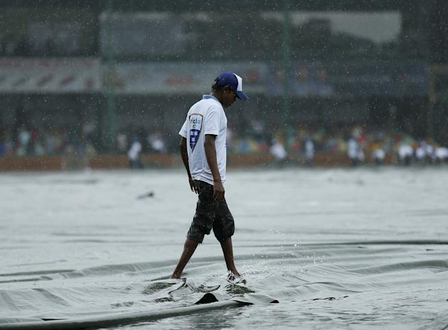 A ground worker walks in the rain after covering the field as the match was stopped due to rain, on the first day of third and final test cricket match between India and Sri Lanka in Colombo
