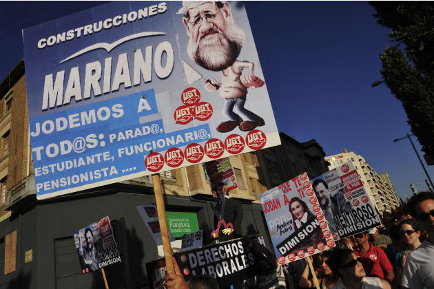 A demonstrator  calling to general strike while he protests against cutback plans by Spain's government holding a banner against Spanish Prime Minister, Mariano Rajoy reading  '' Mariano,