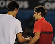 Roger Federer of Switzerland (R) shakes hands with Bernard Tomic of Australia after their fourth-round match at the Australian Open on January 22, 2012. Tomic was left shaking his head in disbelief as he was taken apart by Federer. This time around, his attitude is a little less reverent