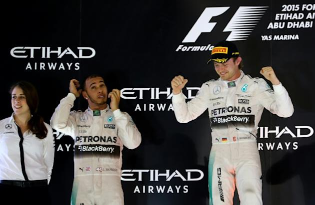 Mercedes AMG Petronas F1 Team's British driver Lewis Hamilton (C) Mercedes AMG Petronas F1 Team's German driver Nico Rosberg celebrate on the podium at the Yas Marina circuit in Abu Dhabi on N