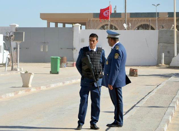 Armed police stand guard in front of the closed border between Tunisia and Libya at Ras Jdir, on November 26, 2015