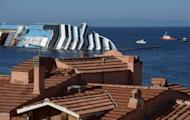 Italian coast guard ships patrol near the stranded Costa Concordia cruise ship, at Giglio Porto, on July 13. For as little as 10 euros, visitors can take a day trip to see the ghostly white wreck of the 114,500-tonne luxury cruise liner, lying on its side after running aground off Giglio Island on January 13, killing 32 people