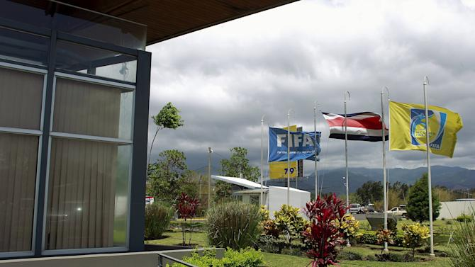 FIFA flags and the Costa Rican national flag are pictured outside Costa Rica's Football Federation offices in San Antonio de Belen