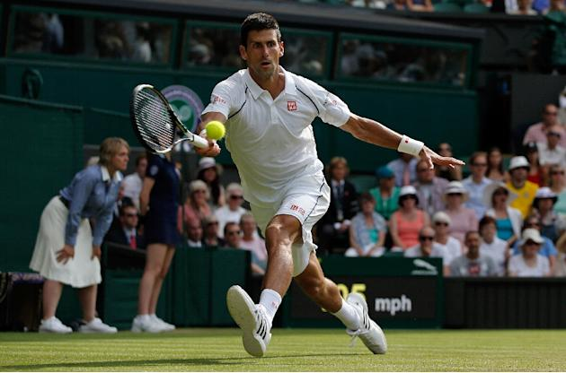 Serbia's Novak Djokovic returns to Australia's Bernard Tomic during their men's singles 3rd round match of the Wimbledon Championships, at the All England Tennis Club in southwest London,