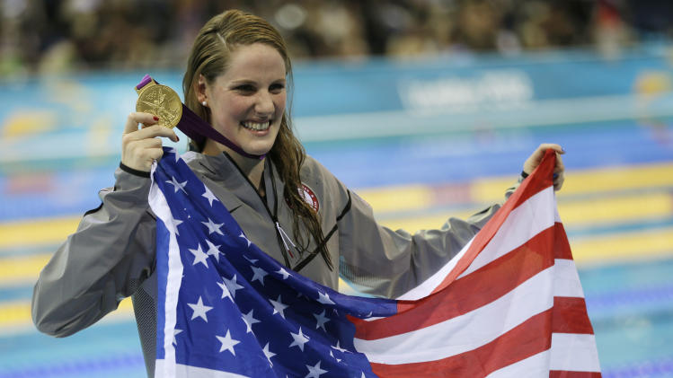 United States' Missy Franklin poses for photographers with her gold medal for the women's 100-meter backstroke swimming final at the Aquatics Centre in the Olympic Park during the 2012 Summer Olympics in London, Monday, July 30, 2012. (AP Photo/David J. Phillip)