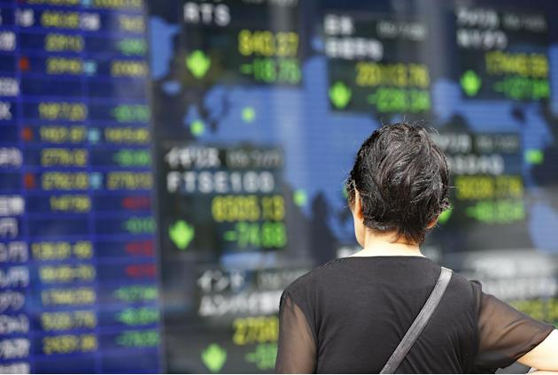 A woman looks at an electronic stock indicator of a securities firm in Tokyo, Tuesday, July 28, 2015. (AP Photo/Shizuo Kambayashi)