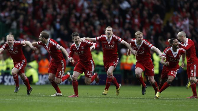 Aberdeen's players react as the winning penalty is taken against Inverness Caledonian Thistle during their Scottish League Cup final soccer match at Celtic Park Stadium