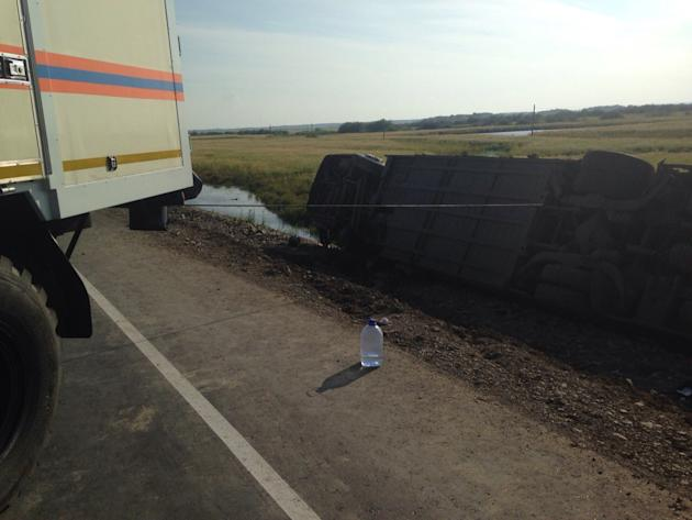 In this handout photo provided by the Far Eastern Branch of the Emergency Situations Ministry, a truck pulls a bus, one of the two that collided on a highway linking Khabarovsk, which sits on the bord