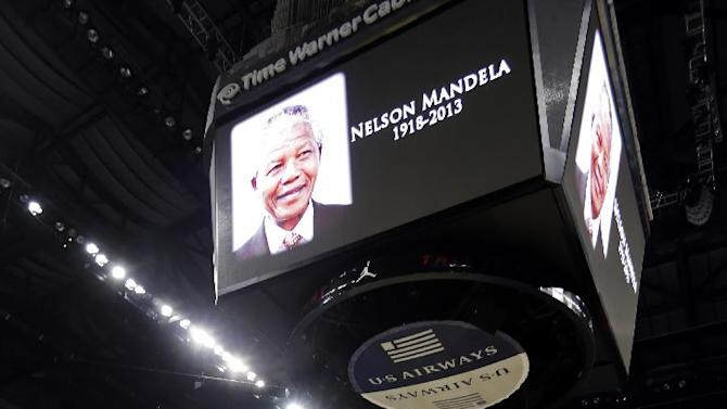 Charlotte Bobcats bow their heads in a moment of silence for former South African President Nelson Mandela, who died Thursday, before an NBA basketball game against the Philadelphia 76ers in Charlotte, N.C., Friday, Dec. 6, 2013