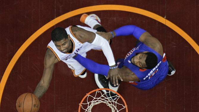 Cleveland Cavaliers' Kyrie Irving, left, shoots against Detroit Pistons' Andre Drummond during the first quarter of an NBA basketball game Monday, Dec. 23, 2013, in Cleveland