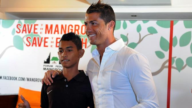 Christiano Ronaldo (R) is reunited with Martunis, an Indonesian survivor of the deadly 2004 Aceh tsunami who the Real Madrid star met in 2005 during a mission to assist tsunami victims, in Kuta on June 26, 2013