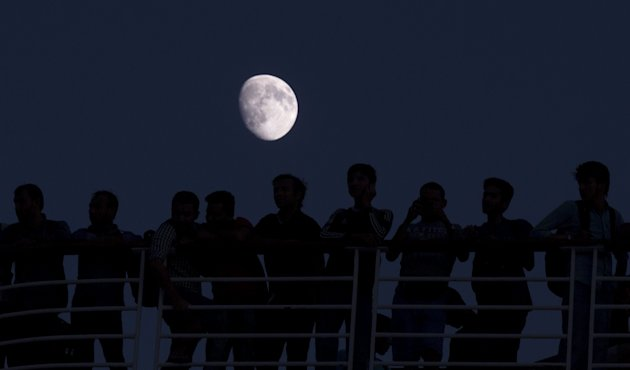 Migrants are silhouetted against the moon as they stand onboard the Eleftherios Venizelos passenger ship at port of Piraeus near Athens, Greece, August 26, 2015. REUTERS/Stoyan Nenov