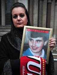 Donna Miller holds a picture of the brother Paul Carlile she lost in the 1989 Hillsborough disaster as she leaves the High Court in central London on December 19, 2012. Families of 96 Liverpool fans crushed to death at the Hillsborough football stadium welcomed a British court decision Wednesday to quash accidental death verdicts from the disaster, but say their fight is far from over
