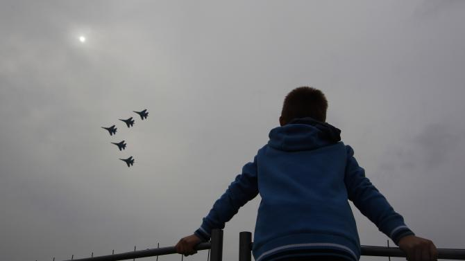 A spectator watches Sukhoi Su-27 jet fighters of the Russkiye Vityazi aerobatic team perform during a demonstration flight at the MAKS International Aviation and Space Salon in Zhukovsky