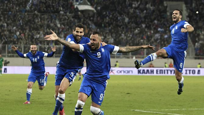 Greece's Kostas Mitroglou, center, celebrates after scoring the third goal of his team against Romania during their World Cup qualifying playoff first leg soccer match at the Karaiskaki stadium in the port of Piraeus, near Athens, Friday, Nov. 15, 2013
