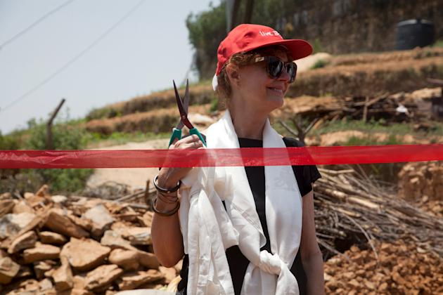 U.S. actress and Academy Award winner Susan Sarandon cuts a ribbon during the inauguration of a programme to build earthquake and wind resistant homes in Ramkot, Kathmandu