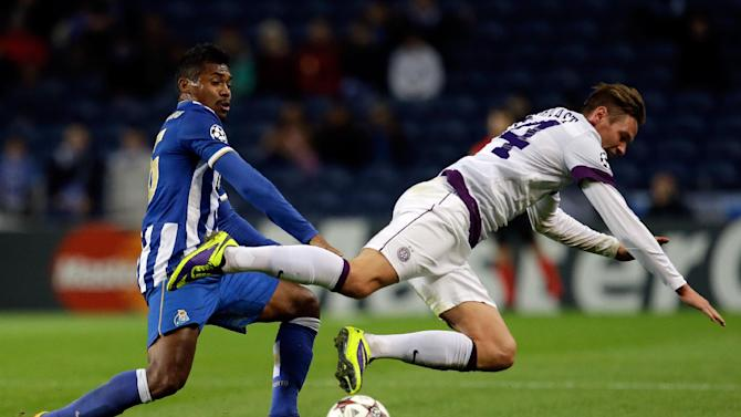 Vienna's Roman Kienast, right, falls in front of Porto's Alex Sandro during the Champions League group G soccer match between FC Porto and Austria Vienna Tuesday, Nov. 26, 2013, at the Dragao stadium in Porto, northern Portugal
