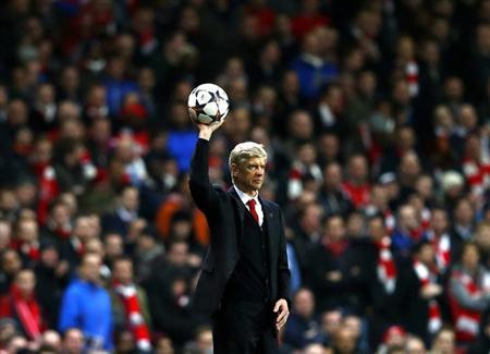 Arsenal's manager Arsene Wenger throws the ball during the match against Bayern Munich in the Champions League round of 16 first leg soccer match at the Emirates Stadium in London February 19, 2014. REUTERS/Eddie Keogh/Files
