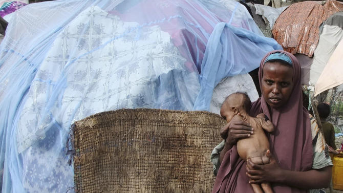A Somali woman from southern Somalia holds her malnourished child in a refugee camp in Mogadishu, Somalia, Wednesday, Aug, 17, 2011. The World Food Program said Saturday that it is expanding its food distribution efforts in famine-struck Somalia, where the U.N. estimates that only 20 percent of people needing aid are getting it.(AP Photo/Farah Abdi Warsameh)
