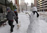 A couple walks their dog past a snowman near the State Capitol building in Indianapolis, Indiana January 6, 2014. REUTERS/Nate Chute