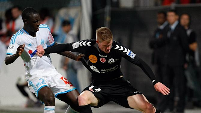 Stade de Reims' forward Gaetan Charbonnier, right, challenges for the ball with Marseille's French defender Benjamin Mendy during their League One soccer match, at the Velodrome Stadium, in Marseille, southern France, Saturday, Oct. 26, 2013