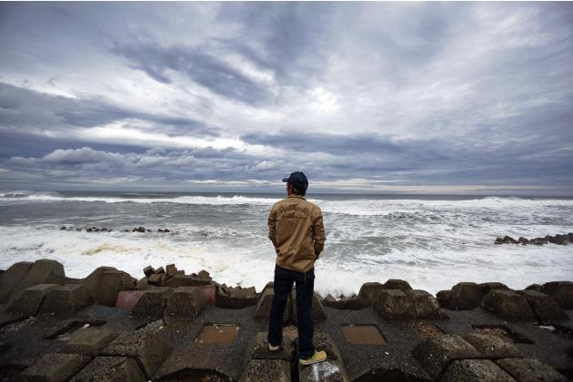 A man watches waves break into anti-tsunami barriers after a storm in Iwaki, Fukushima Prefecture