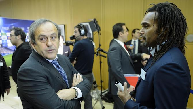 UEFA president Michel Platini, left, speaks with Former French  national soccer player Christian Karembeu, right, before the draw of the round of 16 games of UEFA Champions League 2013/14 at the UEFA Headquarters in Nyon, Switzerland, Monday, Dec. 16, 2013