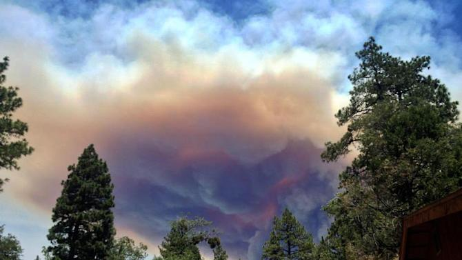 This July 17, 2013 image provided by Meagan Greene shows wildfire smoke near Idyllwild, Calif. The blaze about 100 miles east of Los Angeles had grown to more than 35 square miles in size and had destroyed at least six houses and mobile homes. Tensions heightened late Wednesday after winds shifted, causing the fire to change course and head in the direction of Idyllwild, an artist community and hiking destination in the San Jacinto Mountains.(AP Photo/Meagan Greene)