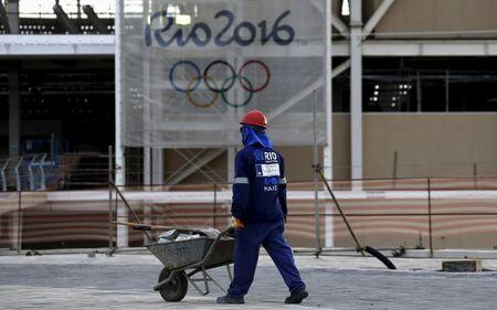 A worker walks in front of the Olympic aquatic venue for the Rio 2016 Olympic Games during the third media briefing for the Games in Rio de Janeiro