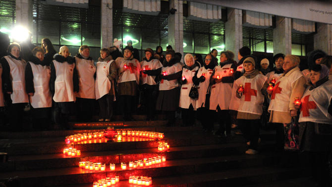Ukrainian people make a red ribbon sign with candles ahead of the World AIDS Day, in Kiev, Ukraine, Thursday, Nov. 29, 2012. (AP Photo / Sergei Chuzavkov)
