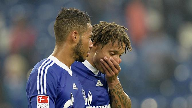 Schalke's Jermaine Jones of the U.S., centre, and Dennis Aogo leave the pitch after losing  the German soccer Bundesliga match between FC Schalke 04 and Bayern Munich at the arena in Gelsenkirchen, Germany, Saturday, Sept. 21, 2013. Schalke was defeated by Bayern,  0-4