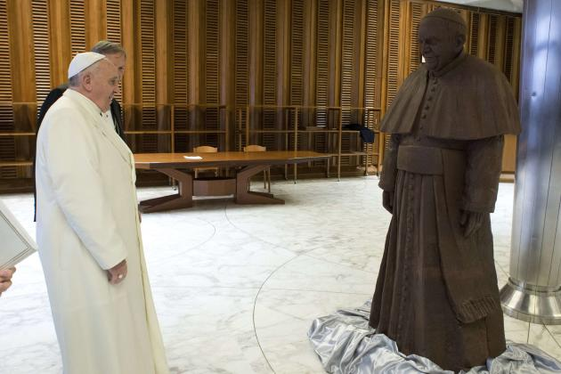 Pope Francis looks at a chocolate statue made in his likeness, which he received as a gift, in Paul VI's Hall at the Vatican