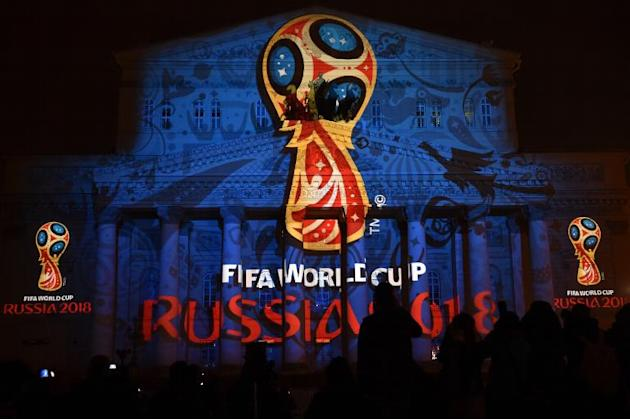 People watch as the facade of the historical Bolshoi Theatre is illuminated with the official emblem of the 2018 FIFA World Cup to be held in Russia in central Moscow on late October 28, 2014