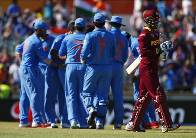 West Indies batsman Denesh Ramdin walks off the field after being bowled by India's Umesh Yadav during their Cricket World Cup match in Perth