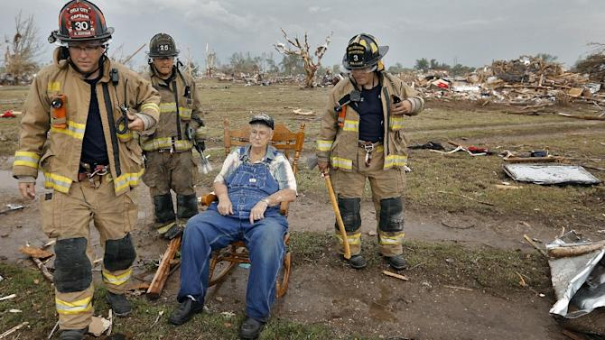 Oklahoma City firefighters check on the status of Gene Tripp as he sits in his rocking chair where his home once stood after being destroyed by a tornado that hit the area, Monday, May 20, 2013 in Oklahoma City, Okla. (AP Photo/The Oklahoman, Chris Landsberger)