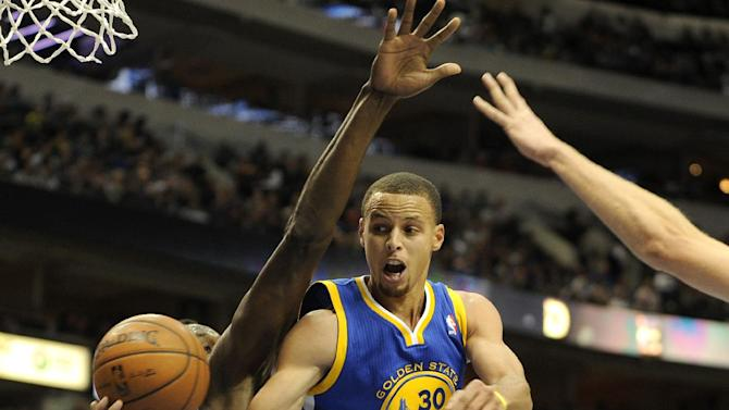 Golden State Warriors point guard Stephen Curry (30) passes around Dallas Mavericks center Samuel Dalembert (1) in the second half during an NBA basketball game on Wednesday, Nov. 27, 2013, in Dallas. The Mavericks won 103-99