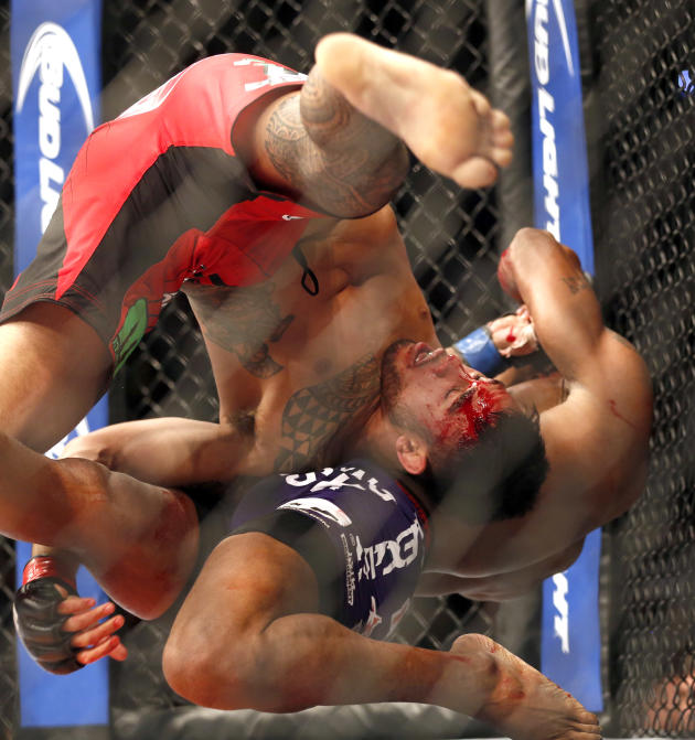 Brad Tavares, front, and Yoel Romero fight in a UFC mixed martial arts event bout Saturday, April 19, 2014, in Orlando Fla. (AP Photo/Reinhold Matay)