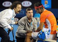 Courtside trainers attend to Rafael Nadal's knee injury during his quarter-final match against Andy Murray at the Australian Open tennis tournament in Melbourne, on January 26, 2010. Nadal had to quit the match with a right knee injury and was out of action for two months
