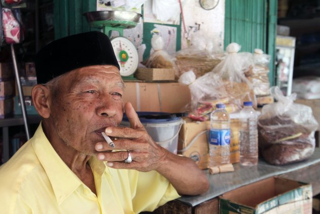 A vendor of locally grown tobacco smokes a cigarette in a market in Banda Aceh June 24, 2014.REUTERS/Junaidi Hanafiah (INDONESIA - Tags: HEALTH)