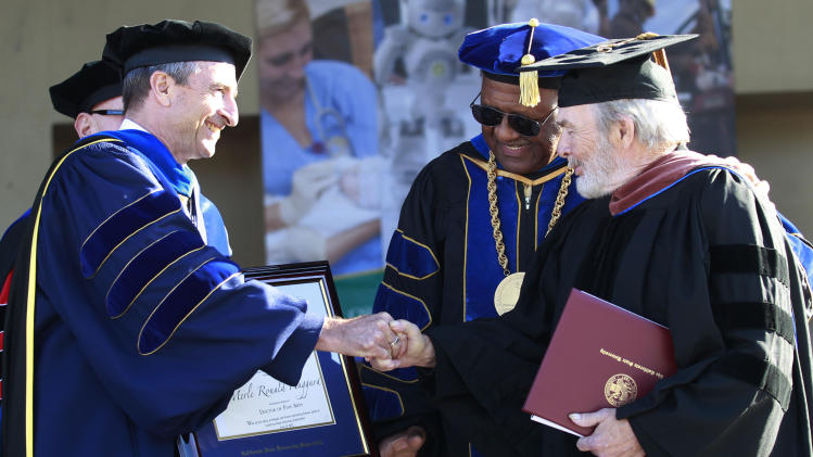 Dr. Richard Collins, Dean, School of Arts and Humanites at CSUB, presents Merle Haggard with his Doctorate of Fine Arts as CSUB President Dr. Horace Mitchell watches at California State University, Bakersfield on Friday June 14, 2013. (AP photo/The Bakersfield Californian, Felix Adamo)