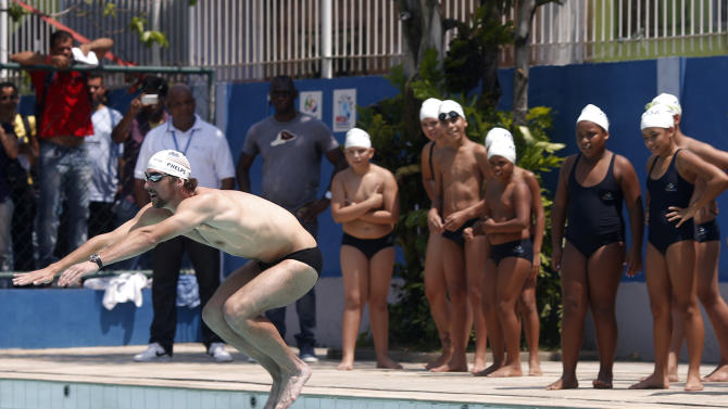 U.S. Olympic swimmer Michael Phelps gives a swimming lesson to youths during a visit at the Alemao slum complex's Olympic Village in Rio de Janeiro