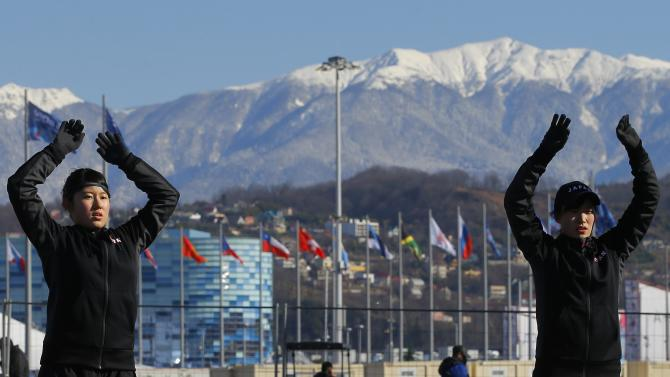 Members of the Japanese women's ice hockey team warm up before practice outside the Shayba arena at the 2014 Sochi Winter Olympics