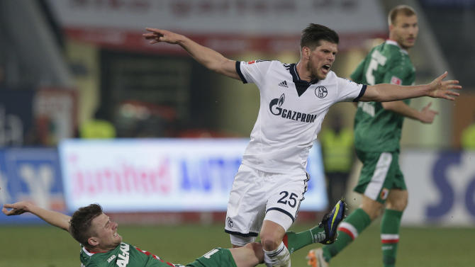 Schalke's Klaas-Jan Huntelaar of the Netherlands, right, and Augsburg's Daniel Baier challenge for the ball during the German first division Bundesliga soccer match between FC Augsburg and FC Schalke 04, in Augsburg, southern Germany, Friday, March 14, 2014