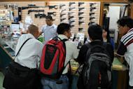 Gun enthusiasts look at guns at a weapons shop in Manila on April 4, 2013. There were 1.2 million registered firearms in the Philippines last year, with another 600,000 unlicensed firearms in circulation, according to national police data