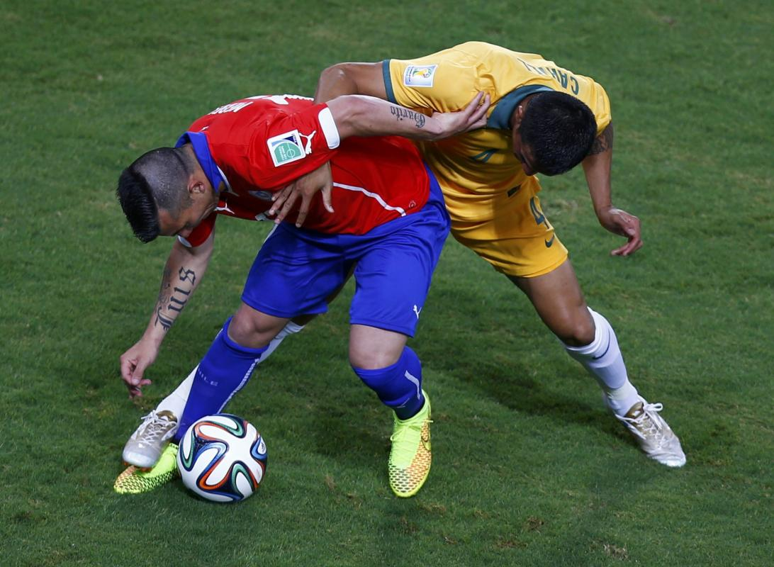 Chile's Medel fights for the ball with Australia's Cahill during their 2014 World Cup Group B soccer match at the Pantanal arena in Cuiaba