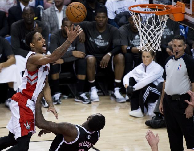 DeMar DeRozan (izquierda) de los Raptors de Toronto intenta anotar sobre Andray Blatche de los Nets de Brooklyn en los playoffs de la NBA el martes 22 de abril de 2014. (AP Foto/The Canadian Press, Na