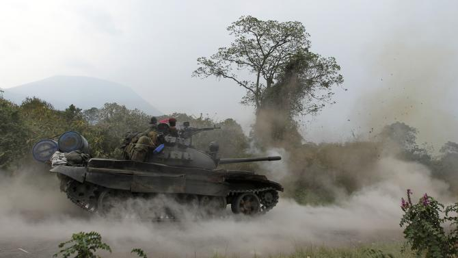 A Congolese armed forces tank fires a shot as soldiers battle M23 rebels in Kibati