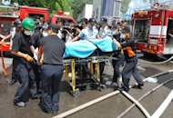 Rescue workers use a stretcher to move a victim (C) of a fire at a construction site in Seoul on August 13, 2012. The fire that engulfed the art museum construction site killed four workers and sent a huge pall of smoke over Seoul on August 13, firefighters said