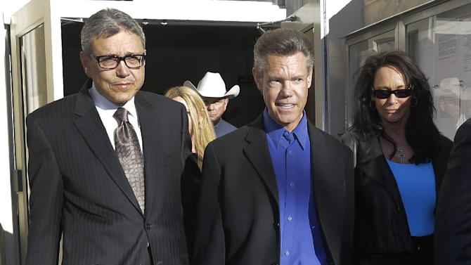 Entertainer Randy Travis, center, exits Grayson County Courthouse with his lawyer Larry Friedman, left, and an unidentified person, right, Thursday, Jan. 31, 2013, in Sherman, Texas. Travis plead guilty to driving while intoxicated in a plea agreement with the court and will pay a $2,000 fine and serve a two year probation. (AP Photo/Tony Gutierrez)