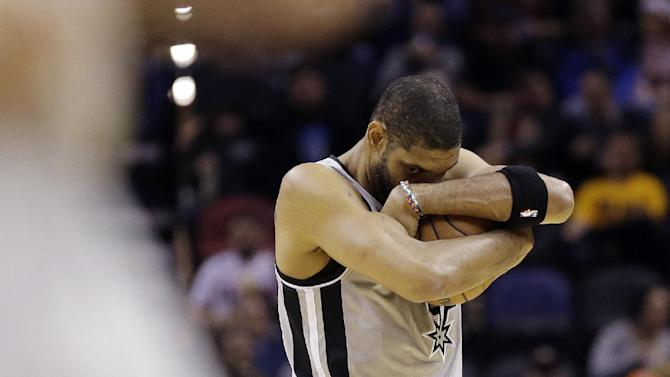 San Antonio Spurs' Tim Duncan covers the ball as he prepares for an NBA basketball game against the Indiana Pacers, Saturday, Dec. 7, 2013, in San Antonio
